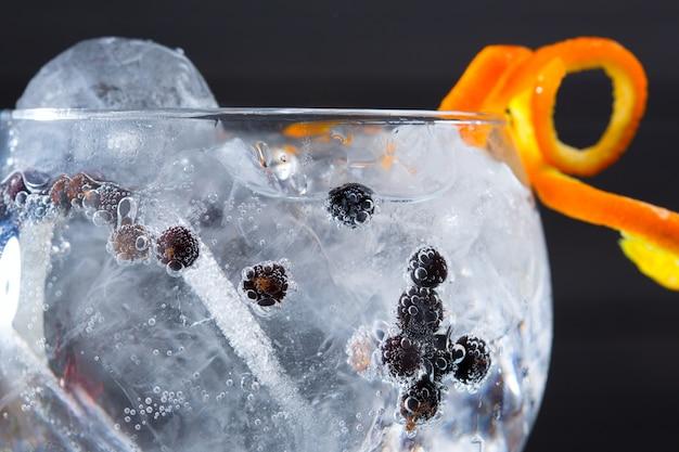 Gin tonic cóctel primer plano macro con bayas de enebro