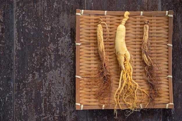Ginseng fresco y seco en la armadura de bambú con el espacio de la copia en el fondo de madera.