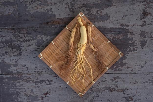 Ginseng fresco y seco en la armadura de bambú con el fondo de madera.