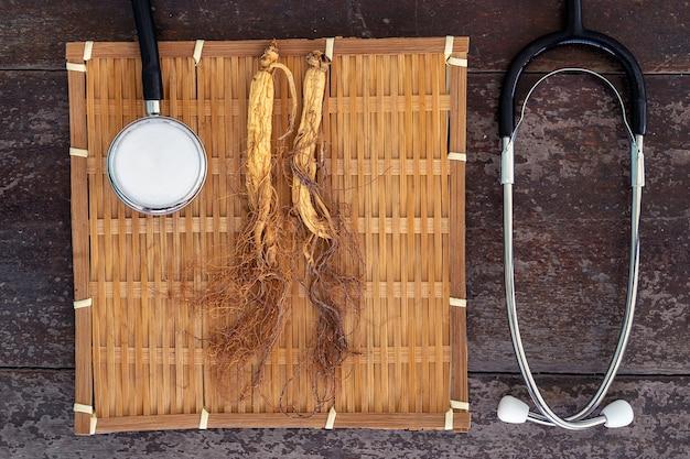 Ginseng seco en tejido de bambú con estetoscopio en el fondo de madera