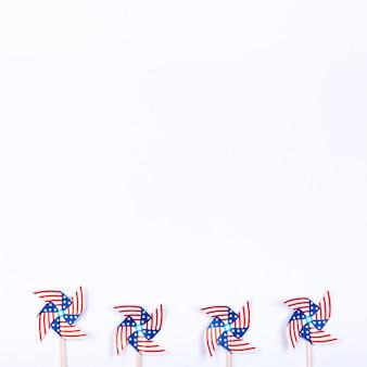 Giradores de viento con símbolo de bandera americana colocados en fila.