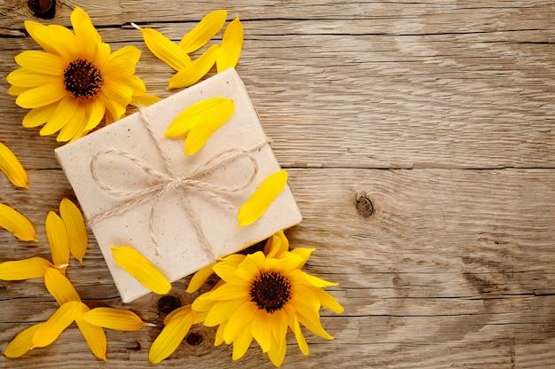 Girasoles ornamentales y caja de regalo sobre fondo de madera