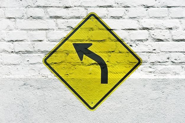 Gire a la izquierda hacia adelante: señal de tráfico estampada en la pared blanca, como graffiti