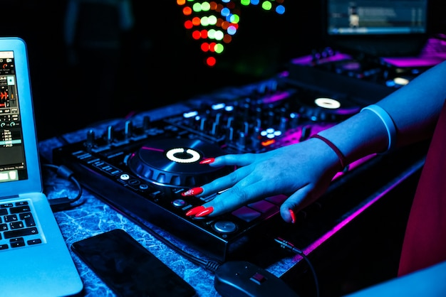 Girl dj mezcla música con sus manos en un mezclador de música en un club nocturno en una fiesta