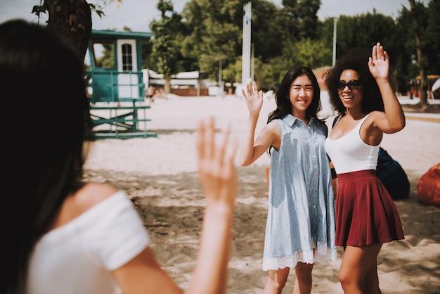 Girl greets friends turistas se reúnen en summer shore