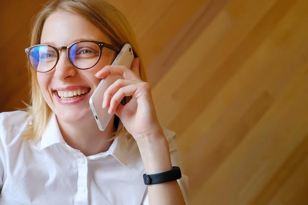 Girl manager, profesional independiente, mujer de negocios con gafas hablando por un teléfono móvil, sonriendo.