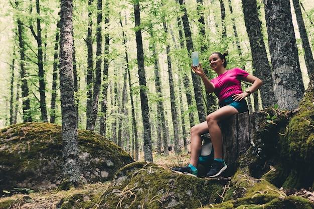 Girl scout haciendo un selfie en el bosque.