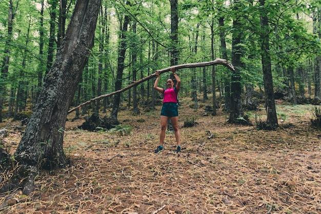 Girl scout levantando una gran rama de árbol en el bosque.