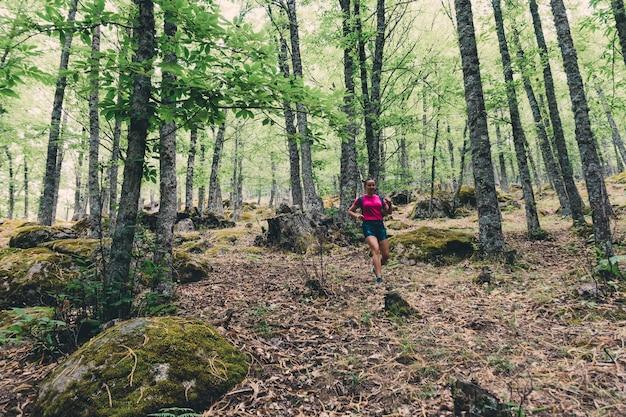 Girl scout con una mochila y un bastón corriendo y caminando en el bosque.
