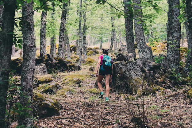Girl scout con una mochila y un bastón de senderismo en el bosque.