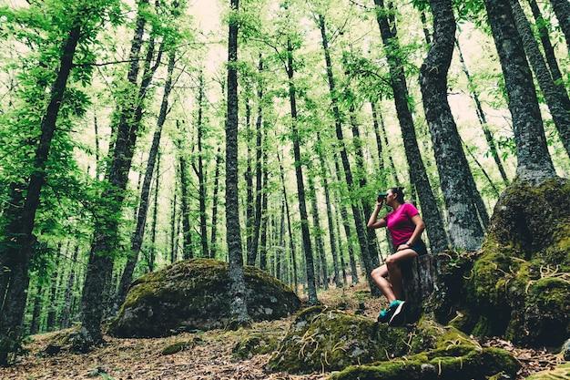 Girl scout con una mochila mirando el bosque con gafas