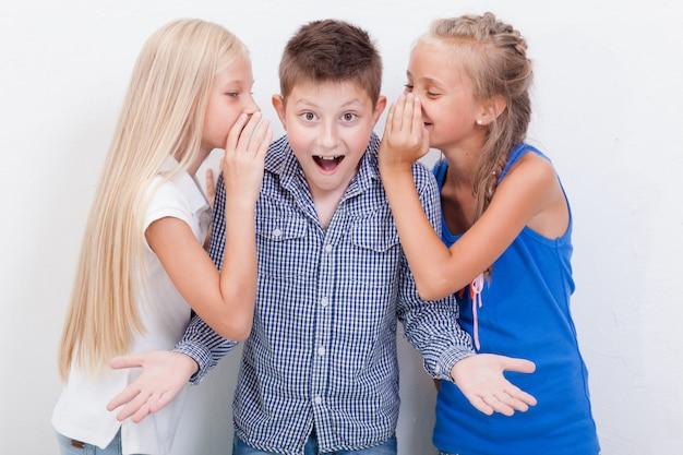 Girsl adolescente susurrando en los oídos de un chico adolescente secreto sobre fondo blanco.