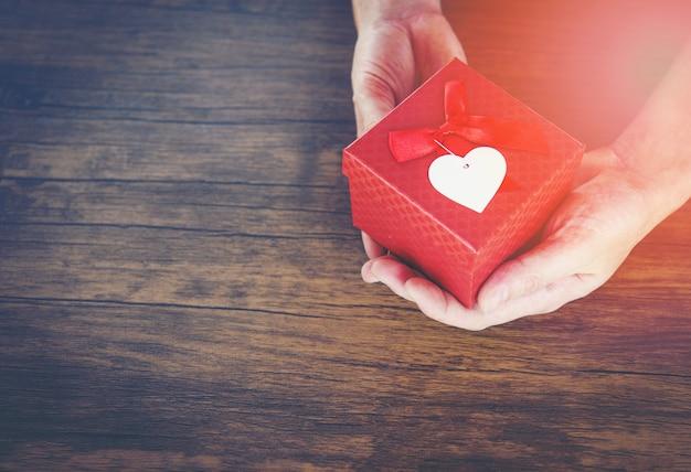 Give love man con una pequeña caja roja presente en las manos con heart for love día de san valentín regalar una caja de regalo con una cinta roja