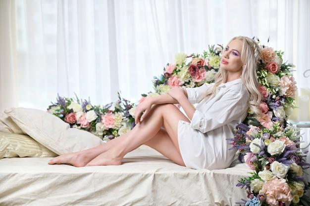 Glamorosa chica rubia con flores.