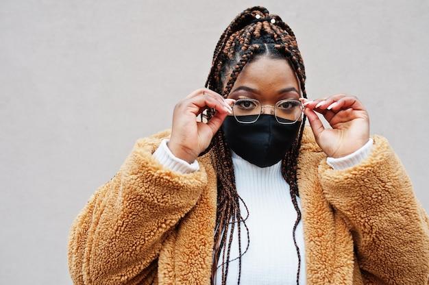 Glamorosa mujer afroamericana en abrigo de piel caliente y mascarilla negra.