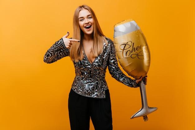 Glamorosa mujer de buen humor que expresa emociones positivas después de la fiesta. hermosa mujer ciega con copa de vino en naranja.