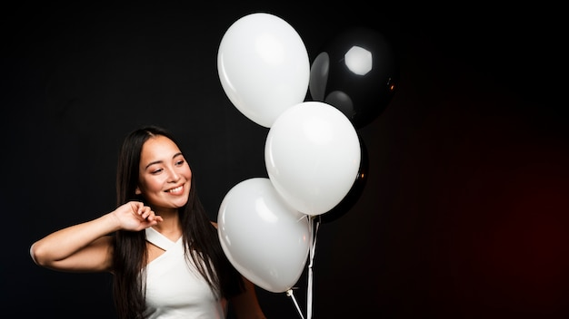 Glamorosa mujer posando con globos en fiesta