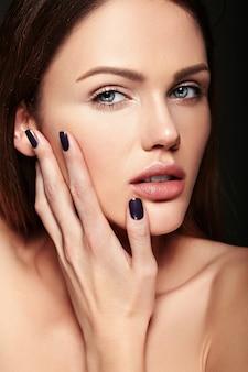 Glamour closeup retrato de belleza de la hermosa modelo de mujer joven caucásica sensual con maquillaje desnudo tocando su piel limpia perfecta posando sobre fondo oscuro