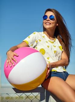 Glamour loco divertido elegante sonriente hermosa joven modelo en ropa casual de verano brillante hipster posando en la calle detrás del cielo azul y sentado en la valla. jugando con coloridos b inflables