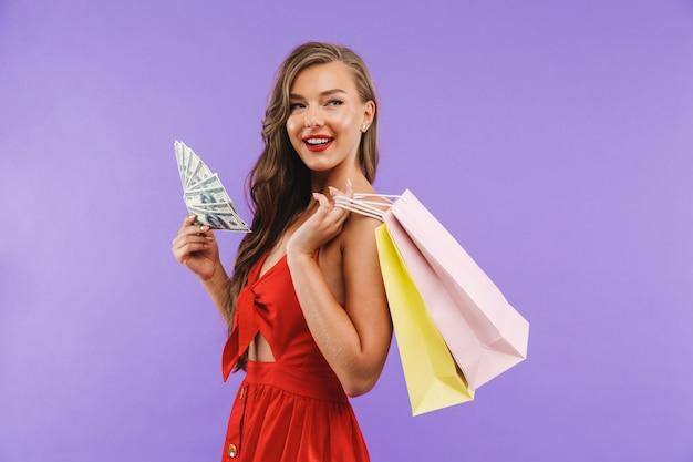 Glamour mujer con vestido rojo sonriendo sosteniendo abanico de dinero y bolsas de papel