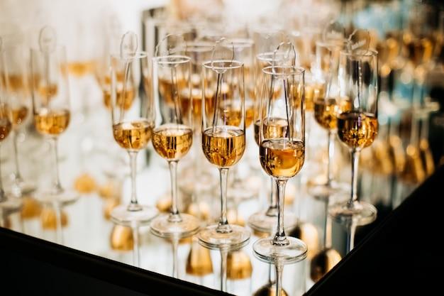 Glaseos champaigne llenos de bebidas alcohólicas en la bandeja con reflejo de espejo