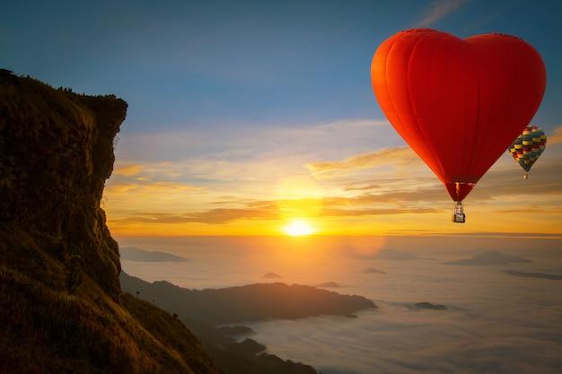 Globo aerostático con forma de corazón sobrevolar la montaña phucheefah