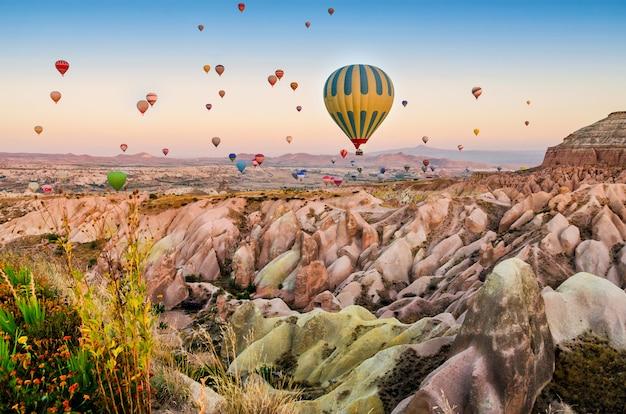 Globo aerostático volando sobre el paisaje de roca en capadocia turquía