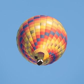 Globo de aire caliente colorido sobre cielo azul