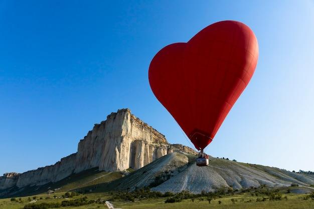 Globo de aire caliente, globo rojo en forma de corazón volador con el telón de fondo de la roca blanca. foto de alta calidad