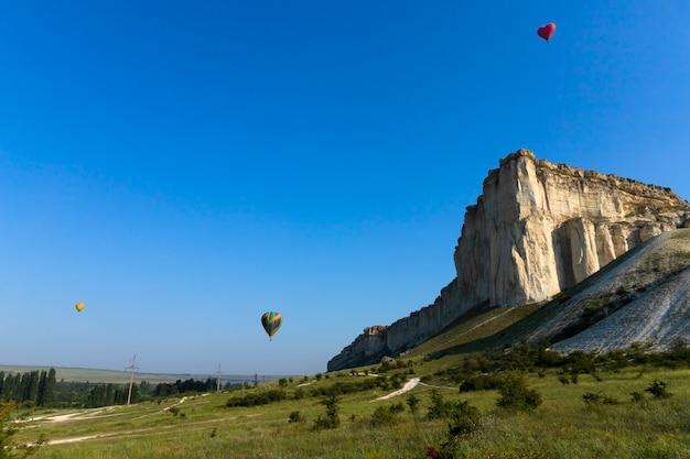 Globo de aire caliente globo rojo en forma de corazón volador con el telón de fondo de la roca blanca