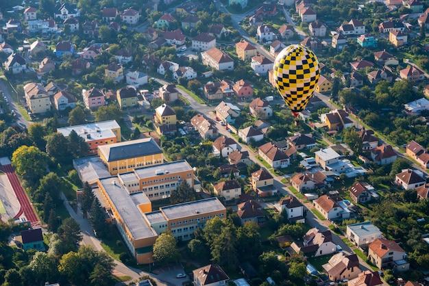 Globo de aire caliente volando bajo sobre la pequeña ciudad checa
