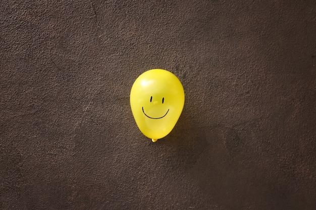 Globo de aire con cara feliz dibujada en mesa oscura
