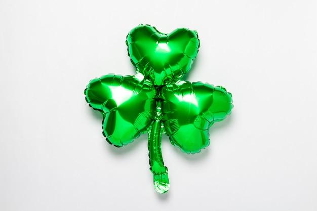 Globo de aire verde trébol sobre una superficie blanca. concepto del día de san patricio, trébol de buena suerte, buena suerte. vista plana, vista superior