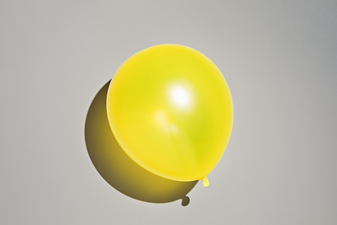 Globo amarillo iluminado sobre la superficie gris definitiva. foto en colores del año 2021