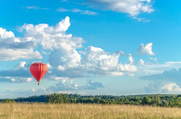 Un globo de avión rojo vuela muy lejos en el horizonte de un cielo azul con nubes