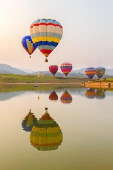 Globo de color de aire caliente sobre el lago con la hora del atardecer