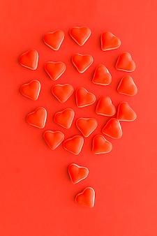 Globo compuesto de caramelos de forma de corazón sobre fondo rojo