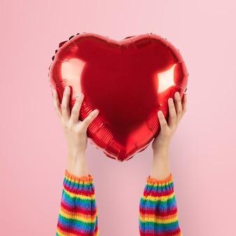 Globo de corazón comunitario lgbtq + sostenido por las manos
