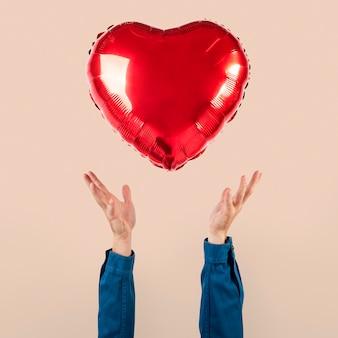 Globo de corazón de san valentín sostenido por una persona