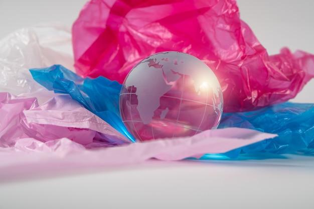 El globo de cristal en una bolsa de plástico. los desechos plásticos desbordan el mundo.