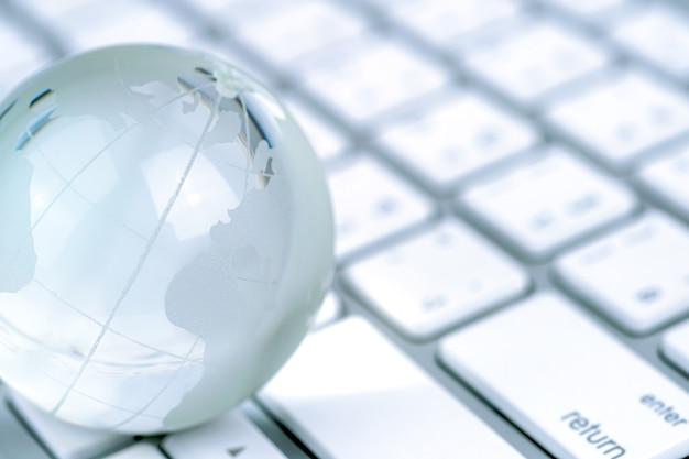 Globo de cristal y economía y negocios mundiales del teclado