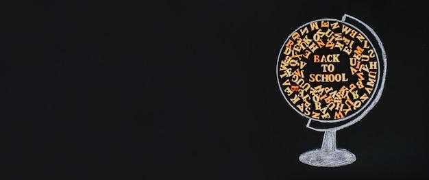 Un globo dibujado con tiza que contiene letras de madera del alfabeto inglés.