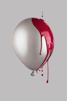 Globo gris cubierto de pintura roja goteando. concepto minimalista creativo.