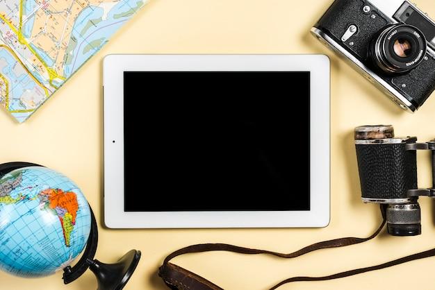 Globo; mapa; cámara binocular y vintage con tableta digital sobre fondo beige.