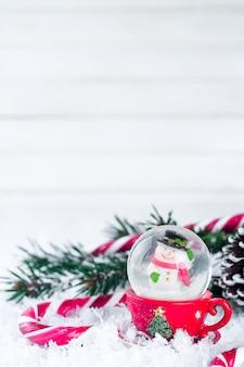 Globo de nieve con muñeco de nieve sobre fondo festivo