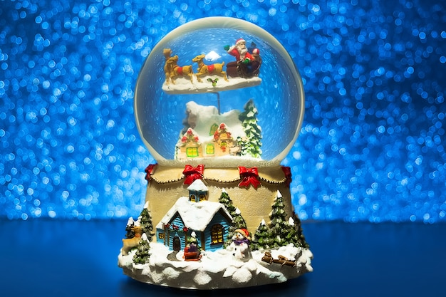 Globo de nieve de navidad. el recuerdo de cristal del año nuevo en el fondo azul de las luces del brillo borroso