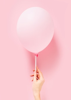 Globo pastel rosa sobre fondo rosa, ligereza, concepto de facilidad