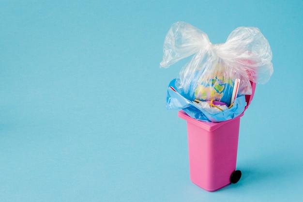 El globo terráqueo se encuentra en la basura. el globo se encuentra en un montón de plástico. contaminación plástica de la naturaleza.