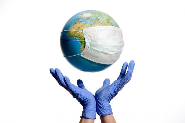 Globo terráqueo con máscara protectora y manos con guantes