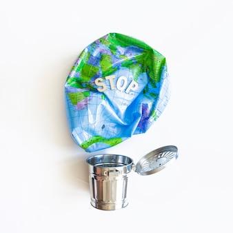 Globo de tierra desinflado y cubo de basura de metal